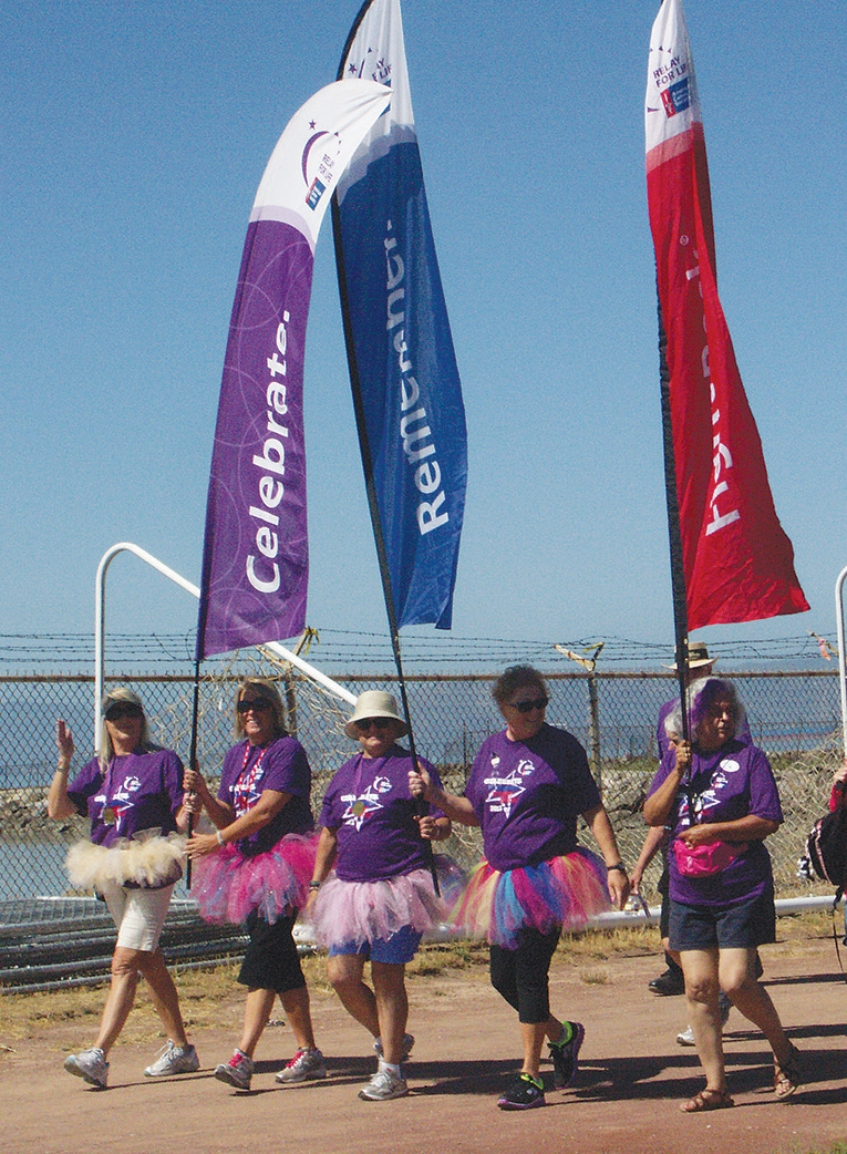 Cancer survivors wearing purple walk the Survivor Lap, the first lap of Relay for Life each year, shown here during the 2013 relay in Alameda.