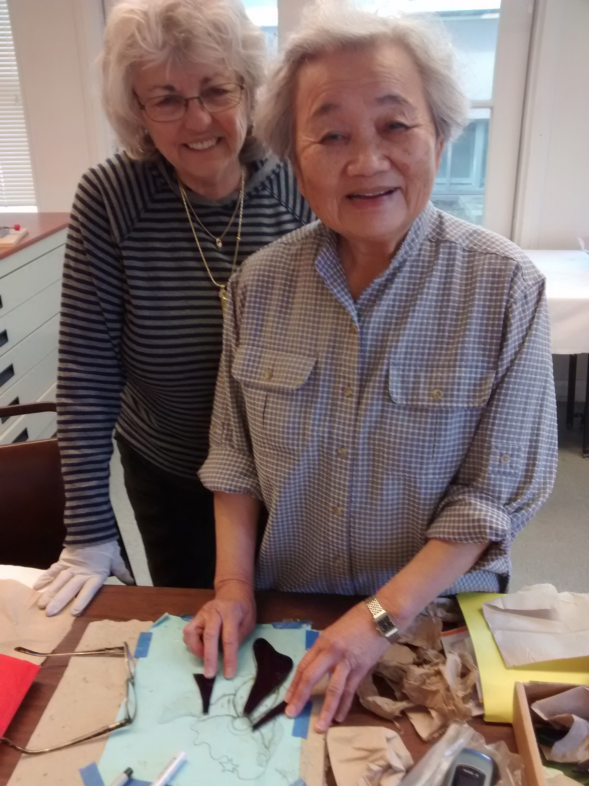 Courtesy photo -- Stained glass class members, Nancy Baldwin, left, and Grace Lin, work on a glass project at Mastick Senior Center.