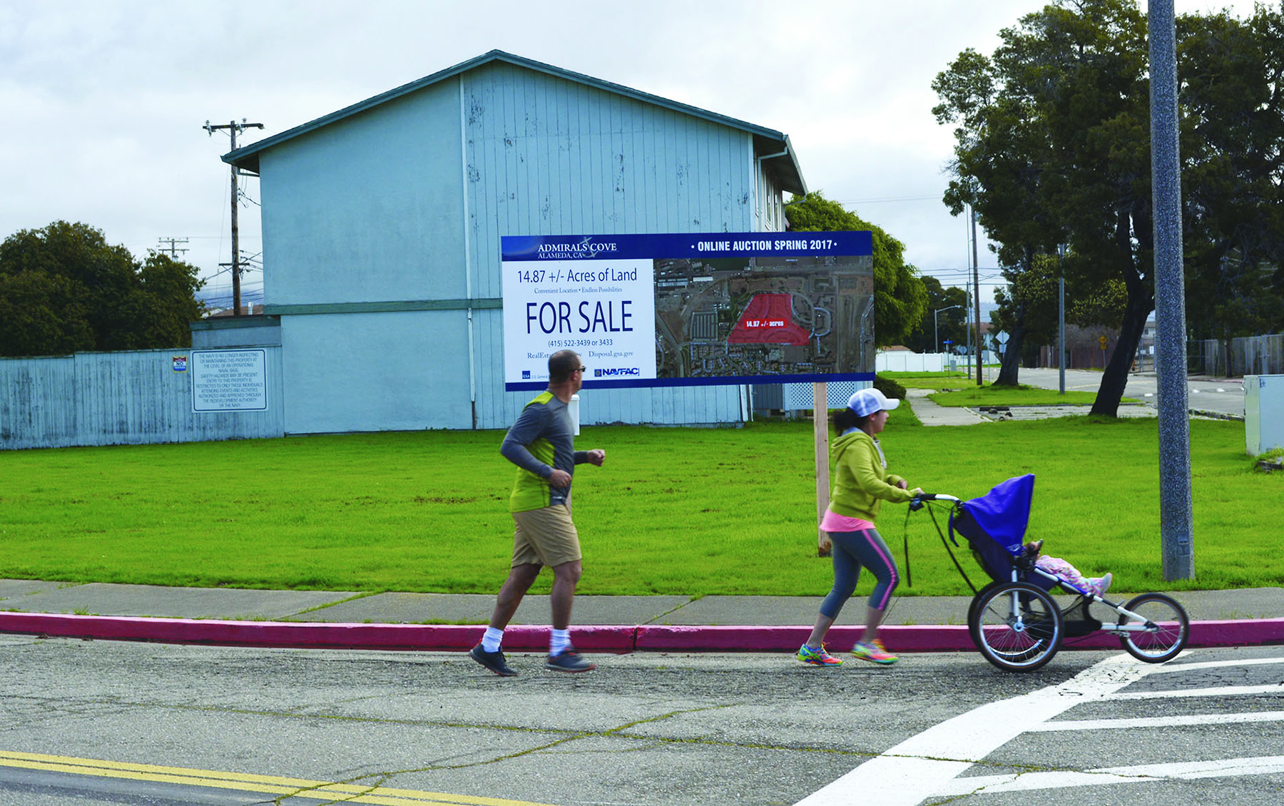 """Richard Bangert  Joggers on Mosley Avenue pass by the Navy's """"For Sale"""" sign. The General Services Administration will auction off North Housing on behalf of the Navy on April 12."""