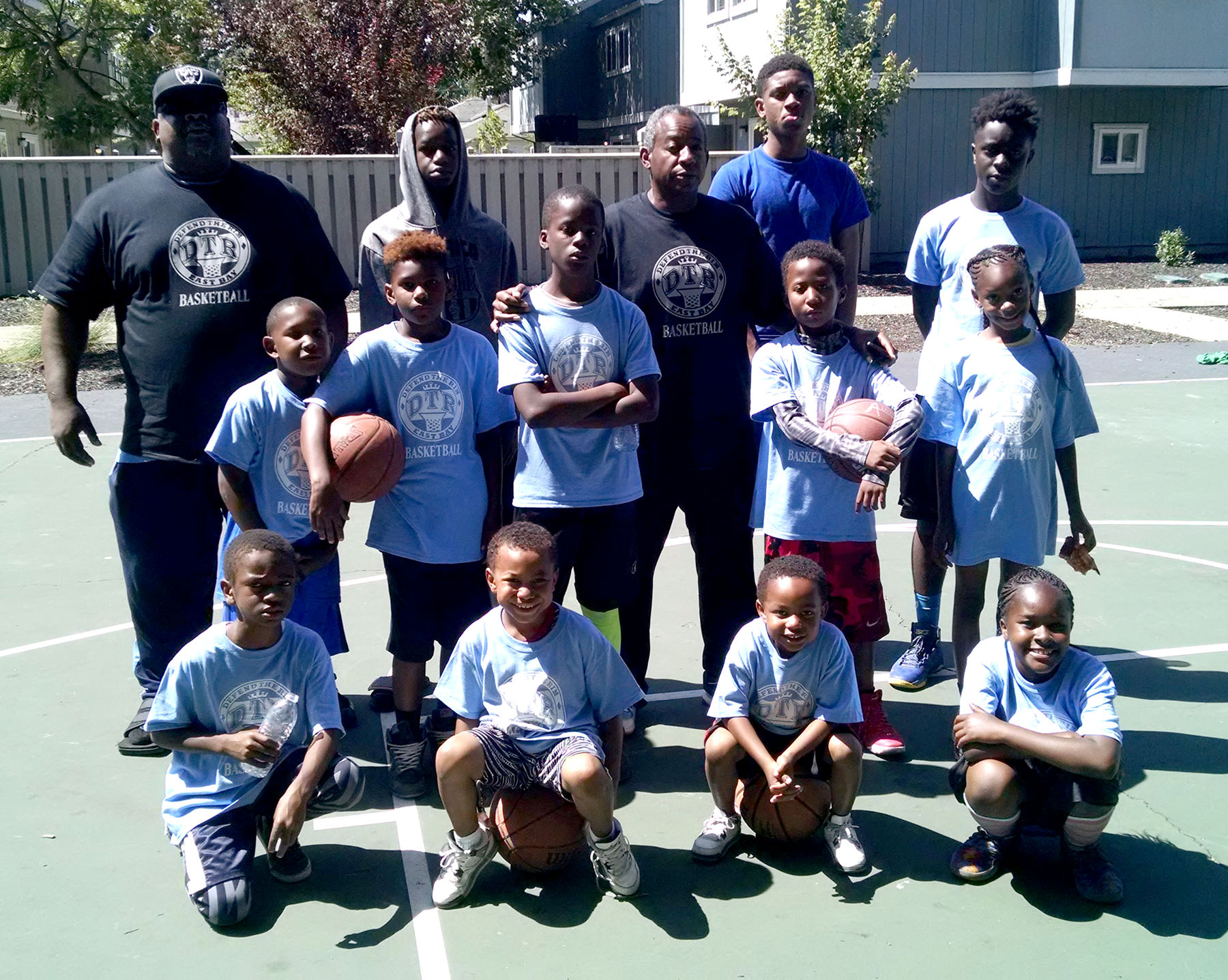 """Dennis Evanosky  Sherman Lee, stands among the youngsters he put through the paces at last Saturday's """"Defend the Rim"""" clinic at the Parrot Village Apartments. Fellow Encinal High School alumnus Jeff Brown, far left, helped Lee with the clinic."""