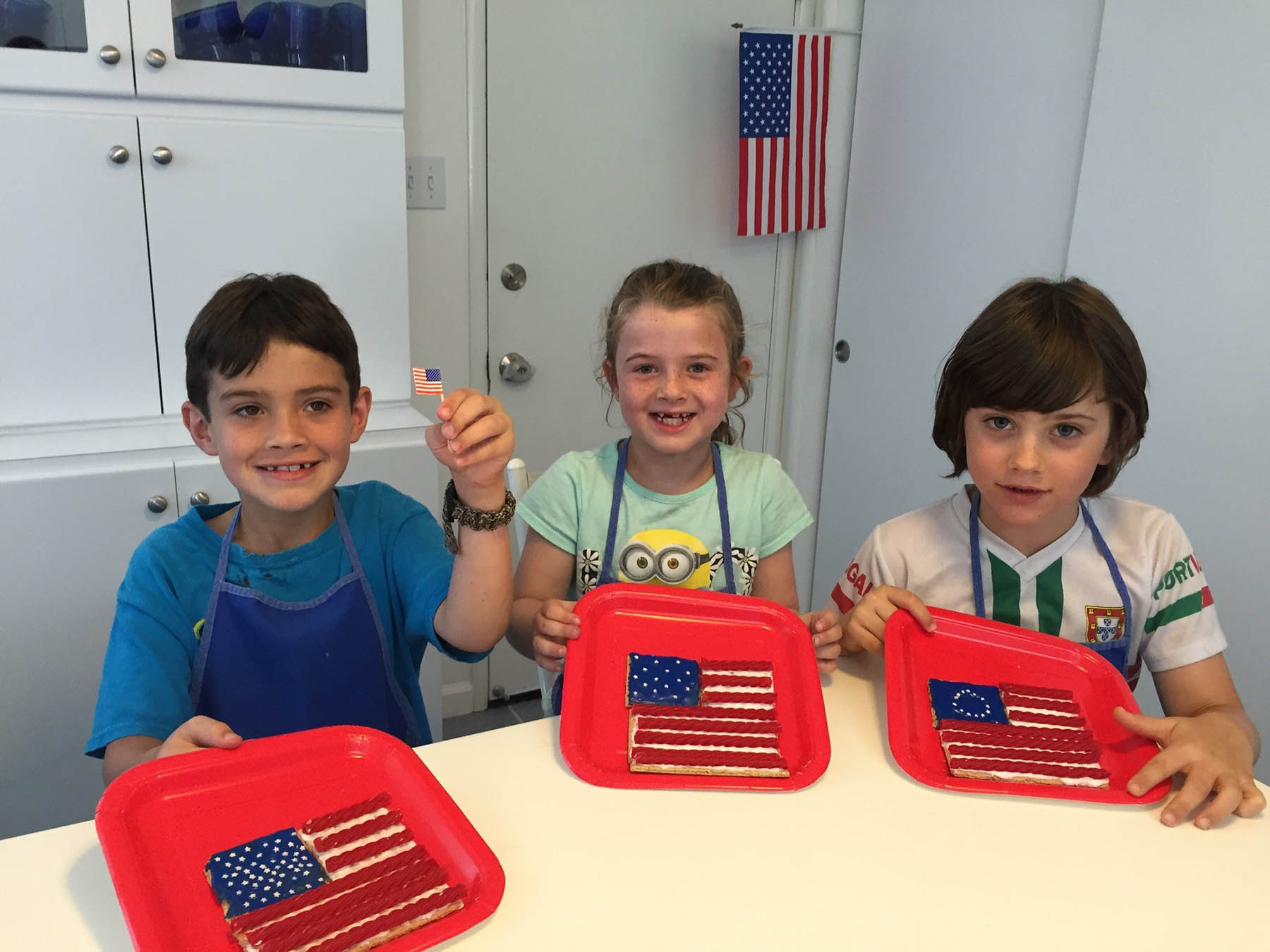 Robin Seeley  Roan, Abby, and Gabe show off their 1959, 1814 and 1776 models of our national flag. Gabe was a special guest from San Francisco.