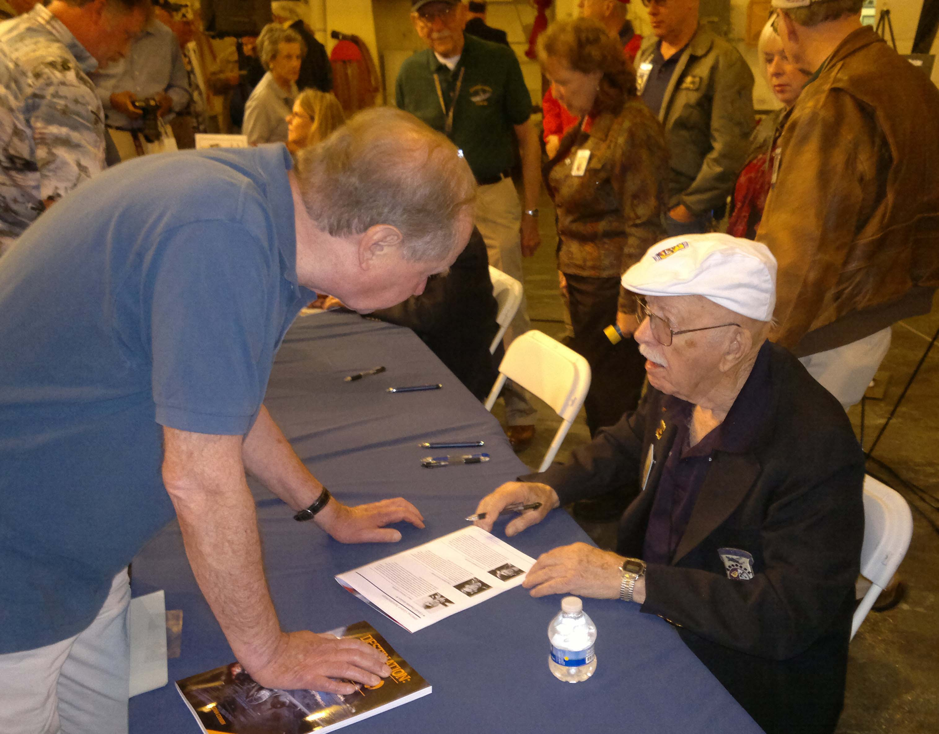File photo Edward Saylor, right, signs autographs at the Doolittle Raid commemoration event aboard USS Hornet in 2012. Saylor flew aboard an aircraft commanded by Lieutenant Donald G. Smith in the daring raid over Japan on Nov. 12, 1942. Saylor is one of the four surviving Doolittle Raiders.