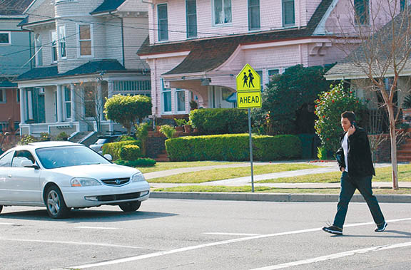 File photo. A pedestrian crosses Grand Street while talking on his cell phone. APD Chief Paul Rolleri expressed his concern about pedestrians being too focused on their devices.