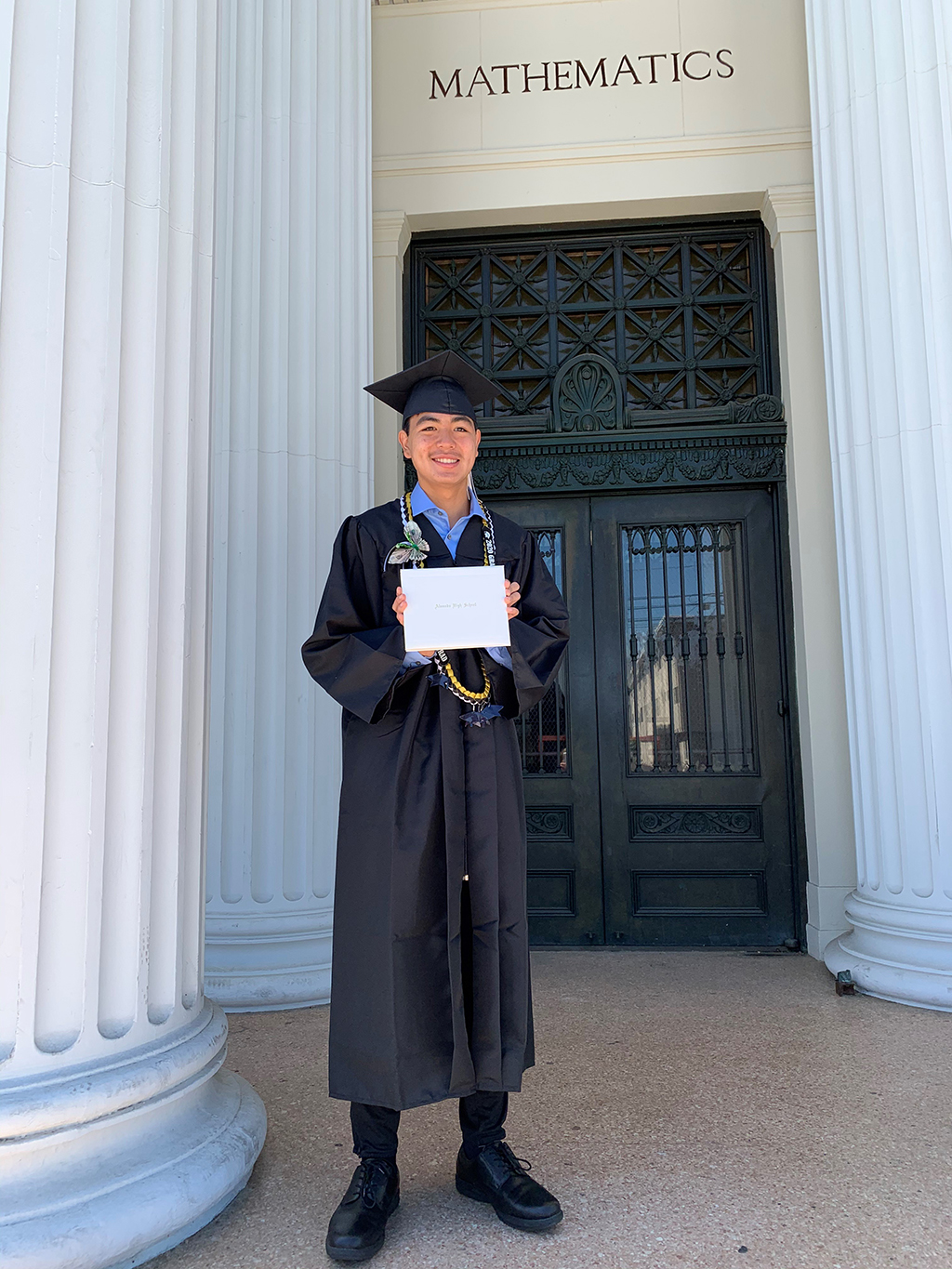 Courtesy photo &nbsp&nbsp Christopher Cheung shows his Alameda High School diploma in front of the refurbished Historical Alameda High School building.