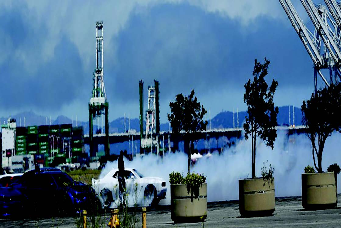 """White smoke spews from cars """"performing"""" an illegal sideshow on July 4 at Alameda Point."""