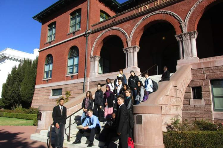 Madeline Eustis  Nea Community Learning Center's mock school board hearing participants paused on the City Hall steps.