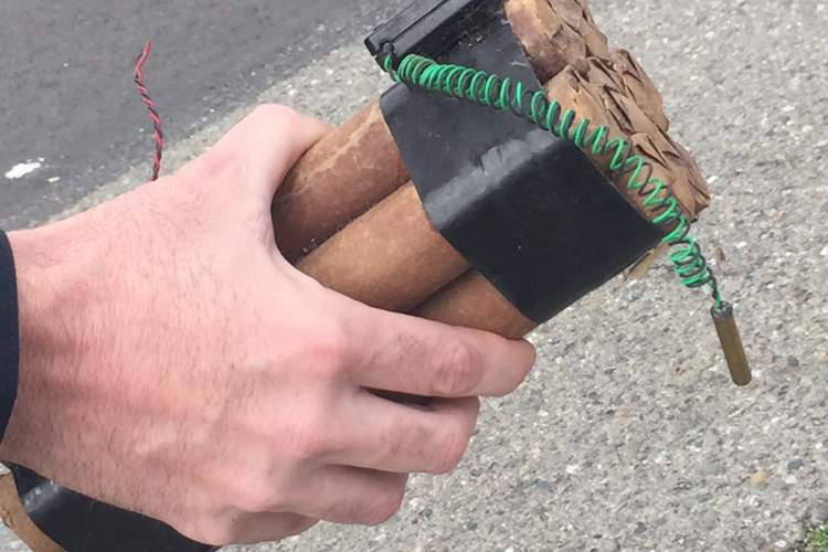 Robert Kahuanui photo. A member of the Alameda County Sheriff Department Explosive Ordnance Disposal (EOD) Squad holds a bundle of what appears to be six sticks of dynamite. Further inspection revealed that the bundle was a movie prop.