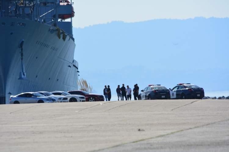 Photo by Richard Bangert Alameda Police speak to drivers who apparently were driving recklessly (below) in the shadow of the USS Keystone State at Alameda Point last Saturday.