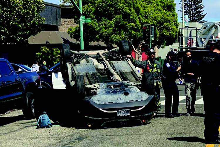 Police and fire department members investigate what caused this automobile to rollover on Monday, June 28.