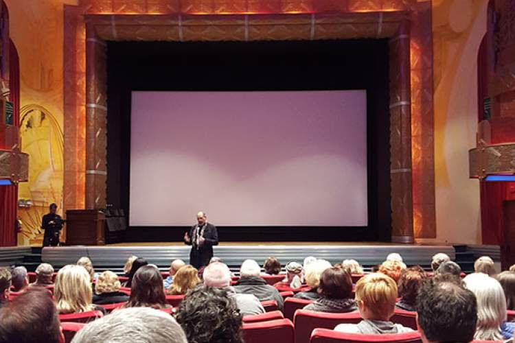 Eric J. Kos photo. Documentary director Jamie Longhi addresses the audience during the question-and-answer period following a screening of Longhi's first film, Shallow Waters: The Public Death of Raymond Zack, at the Michaan Auction House Theater at Alameda Point.