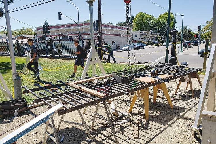 Eric J. Kos &nbsp&nbsp Pete Calahen of Williams Welding leans into his drill as he works to repair the 1879 fence lining the High Street side of Lincoln Park (background). A portion of the fence was knocked off its concrete foundation when an alleged drunk driver struck it.