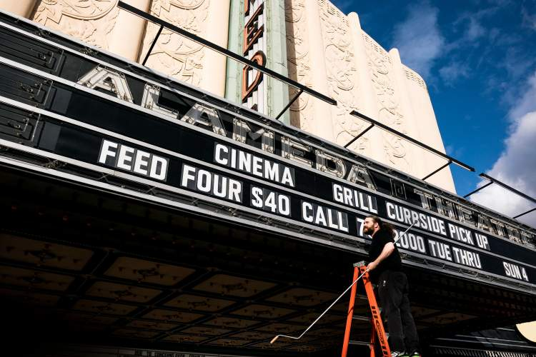 Maurice Ramirez Photography &nbsp &nbsp An employee with Alameda Theatre & Cineplex reconfigures the marquee not to announce the latest release, but to encourage locals to order take out from the adjoining Cinema Grill. The theater is closed at this time.
