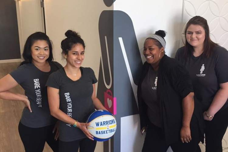 """Courtesy photo  Guests and waxologists at Lunchbox sign a """"rally ball"""" to share their support of the Warriors' """"smooth moves."""" Left to right are local waxologists Yumaya, Gloria, Tashawna and Jessica."""