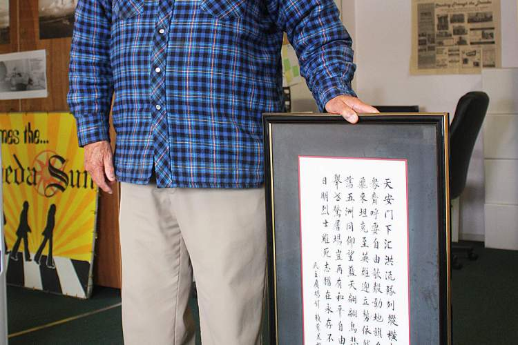 """Dennis Evanosky  Lyle La Faver holds a translation of his poem """"Death on the Square."""" The actions of the Chinese at Tiananmen Square in the summer of 1989 so impressed La Faver that he wrote a poem about the events. His poem so impressed one of his colleagues that the colleague translated the poem into Mandarin."""