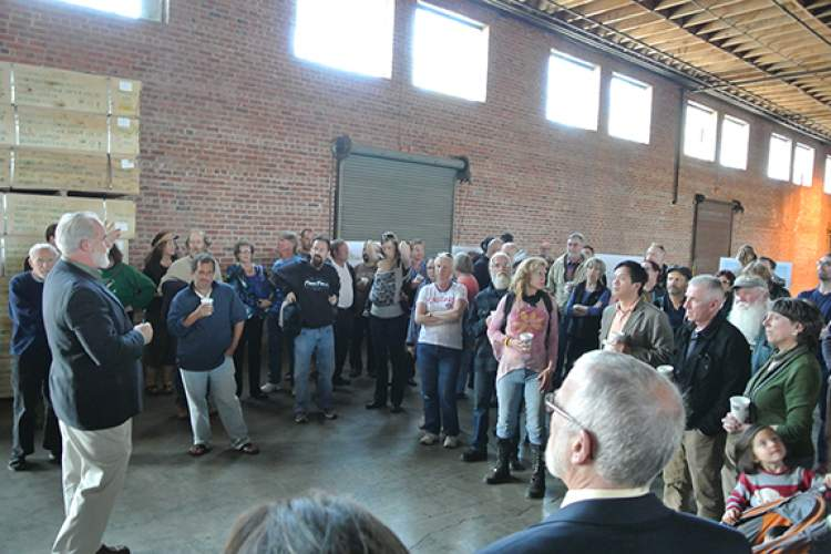 A representative of Tim Lewis Communities addresses the substantial crowd at a specially held tour of the Del Monte Warehouse for members of the Planning and Historical Advisory boards as well as the public last Wednesday, April 23. Photo by Michael Schiess