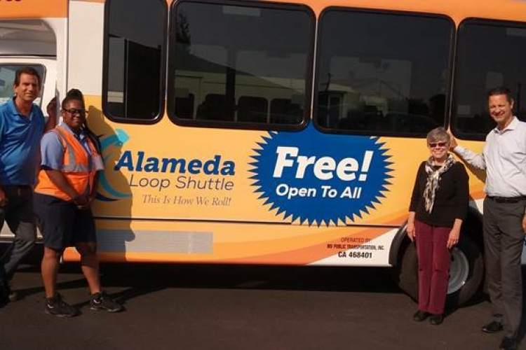 Photo by Henry Dixon. An Alameda Loop Shuttle appears with, from left to right: Brock Keck, maintenance manager; Alasha Campbell, shuttle driver; Victoria Williams, City of Alameda paratransit coordinator and Gregg Eisenberg, general manager.