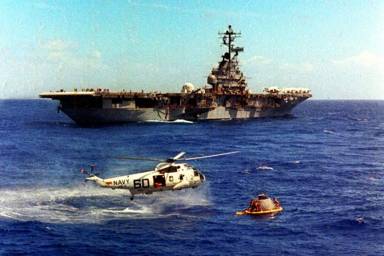 Photo by PHC Milt Putnam, USN (Ret) &nbsp&nbsp This famous July 11, 1969, photograph actually depicts Navy personnel practicing to recover the Apollo 11 spacecraft. Navy swimmers finish attaching the flotation collar around a dummy capsule, with USS Hornet in background.