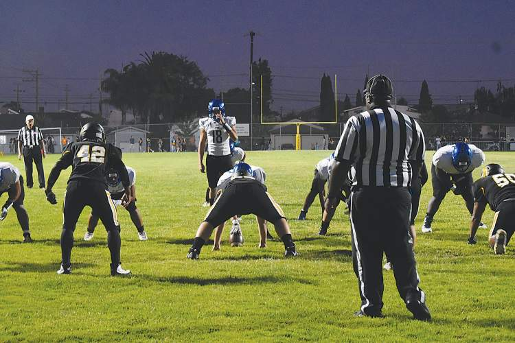 All photos EHS senior A.J. Falk &nbsp&nbsp Encinal High School senior quarterback David Romero-Reinholz surveys the Alameda High School defense before taking the snap at the 65th Island Bowl last Friday, Sept. 13, at Thompson Field.