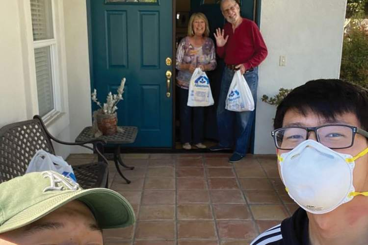 Courtesy photo &nbsp&nbsp Project Gloves volunteers deliver groceries to an elderly couple, while also making sure to keep their distance.