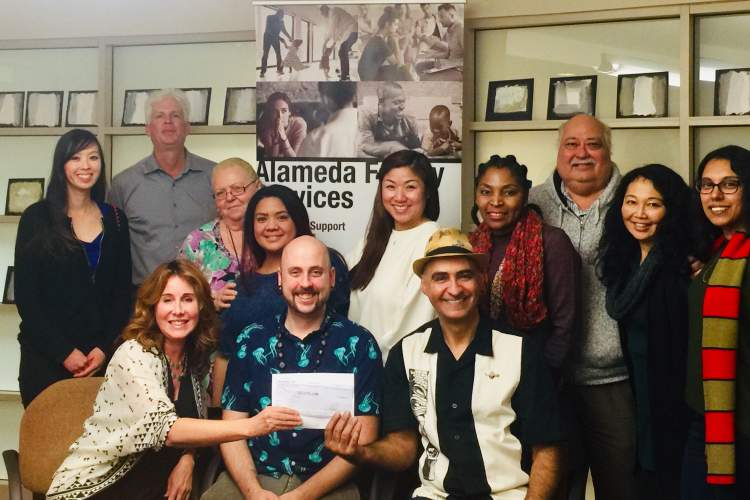 Betty Young &nbsp&nbsp Katherine Schwartz, Alameda Family Services (AFS) executive director, and AFS staff, accept a check from Forbidden Island owner, Michael Thanos.