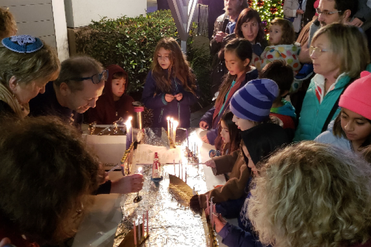 Courtesy photo. Temple Israel's celebration last year brought light to South Shore Center. This year's event also features a table for the public to light their own menorahs Monday, 23.