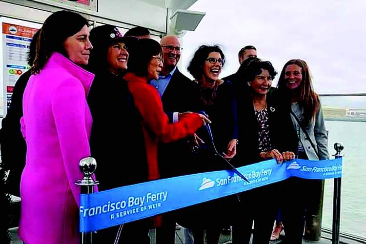 Alameda County Supervisor Wilma Chan, left center in red, and Mayor Marilyn Ezzy Ashcraft hold the scissors in anticipation of cutting the ribbon to initiate ferry service at Seaplane Lagoon.