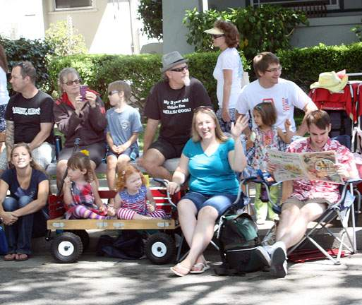 spectators on the parade route one reading Alameda Sun event program
