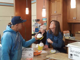 Dennis Evanosky &nbsp&nbsp Jeff Cambra receives a free N95 mask from Jackie Krause at the Mastick Senior Center. The city had a limited supply of masks to give out thanks to Euge Lee's donation.