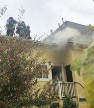 Alameda Fire Department &nbsp&nbsp Alameda firefighters negotiate the roof as smoke pours from a fire at a four-unit apartment building on Lincoln Avenue last Monday.