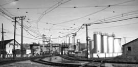 Ralph Demoro &nbsp&nbsp Tracks curving in from the right once carried Big Reds from today's Fernside Boulevard on their way to the Fruitvale Bridge. The tanks on the right were part of a Signal Oil distribution center. Most of the rails in this photograph were torn up in the 1960s to create Tilden Way. However, the Union Pacific retained a right of way on the west side of Tilden that ran from the Fruitvale Bridge to Broadway near Clement Avenue.