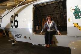 """Courtesy photo  USS Hornet's new executive director Jill Knowland Rapposelli sits in the cabin door of a replica of """"Helo 66,"""" the SH-3H Sea King that recovered the Apollo astronauts. The helicopter is painted in the same """"66"""" livery as the original."""