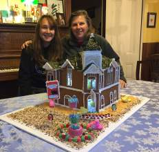 Courtesy photo  Donna Eyestone and her daughter, Emma, show off their gingerbread creation of the Victorian-era building that is home to the Black Pug Café.