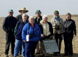 Courtesy photoGolden Gate Audubon members join Alameda bird lovers and staff from the East Bay Regional Park District to display one of the signs recently installed on Crown Beach. The signs call attention to the snowy plovers roosting on the shoreline.