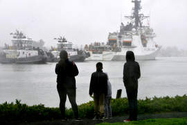 U. S. Coast Guard &nbsp&nbsp Family members look on from the shore as a pair of escort tugs accompany Alameda-based United States Coast Guard Cutter Bertholf through the Oakland Estuary on Jan. 20. On March 24 and 25, the Bertholf joined the U.S. Navy's Missile Destroyer USS Curtis Wilbur on a transit through the Taiwan Strait.