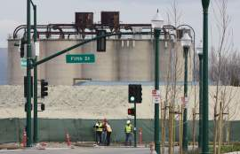 The 80-year-old Santa Cruz Portland Cement Company silos and an impressive ridge of dirt waiting to serve as fill serve as backdrop for an Alameda Municipal Power crew as they survey Fifth Street with contractors in the heart of Alameda Landing. Tuesday City Council considered how to pay for the work at Alameda Landing. Photo by Dennis Evanosky