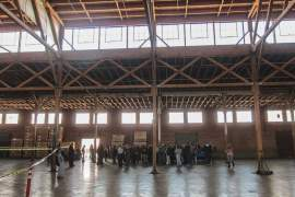 Folks gather to hear from developers under the impressive exposed wooden beams at the Del Monte warehouse, left. Above, the plan shows the center of the warehouse converted to a four-story apartment building. Photo by Maurice Ramirez