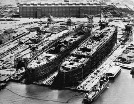 """Two of the eight troop ships built during World War II stand on the shipways at the Bethlehem-Alameda Shipyards on the Oakland Estuary. The turbo machine shop — the """"Red Brick Building"""" — stands just south of the shipways. The building came down in 1985."""