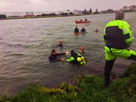 Oakland Fire Department Photo. Members of the Alameda and Oakland fire departments rescue a man who drove his taxicab into the waters off Doolittle Drive last Sunday morning.