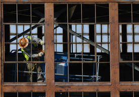 Richard Bangert &nbsp&nbsp A worker grinds a metal frame on Building 9, preparing to replace more than 9,000 window panes. Workers have already applied rust-converting primer to the frames.