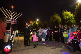 Clayton J. Mitchell Photography &nbsp&nbsp Rabbi Meir Schmotkin of Chabad of Alameda (holding torch) says a few words to mark the celebration of Hanukkah in Alameda last Sunday. Mayor Trish Spencer lit the first candle on the 9-foot menorah shown at left.