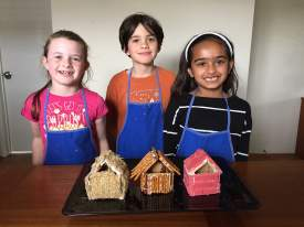 Photos by Robin Seeley  The three little cooks: Abby, Roan and Leila, happily pose with their construction projects before the Big, Bad Wolf's visit to their houses made of straw (shredded wheat), sticks (pretzels) and bricks (Bazooka bubble gum)