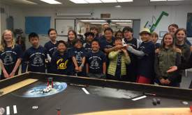 Alameda Education Foundation  Wood robotics champions celebrate their win with a trophy made with a 3-D printer while other participants look on.