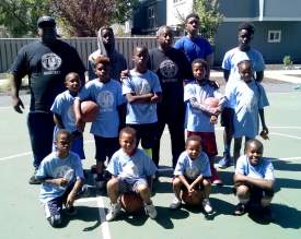 "Dennis Evanosky  Sherman Lee, stands among the youngsters he put through the paces at last Saturday's ""Defend the Rim"" clinic at the Parrot Village Apartments. Fellow Encinal High School alumnus Jeff Brown, far left, helped Lee with the clinic."
