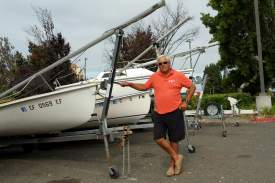 Dennis Evanosky  Robert Nelson stands next to one of the three small sailboats that he and fellow members of the Gate 11 Yacht Club use for races. The boats are among those parked in the Extended Stay parking lot on Marina Village Parkway.