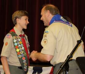 Troop 16 Scoutmaster Tim Riley congratulates Dallin Stewart, 13, on earning his Eagle Scout rank.