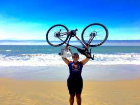 Courtesy photo  Emily Lovell lifted both her bike and her Alameda Sun high in celebration after riding more than 4,000 miles across the country.