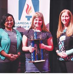 Alameda County Office of Education photo.  Ella Banchieri displays her second-place spelling bee trophy. Banchieri is flanked by left, Aisha Knowles, Alameda County Board of Education Trustees and right, Dawn O'Connor,  Director of STEM and Science Partnership at the Alameda County Office of Education.