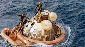 Courtesy NASA &nbsp&nbsp Few know the story of the U.S. Navy Frogman, John Wolfram, who became the first person the Apollo 11 astronauts saw upon their return to Earth. Wolfram can be seen standing at the top of the capsule with flower decals on his wetsuit.
