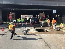 City of Alameda photo. An Oakland Public Works crew works to fill the sinkhole and restore the pavement.
