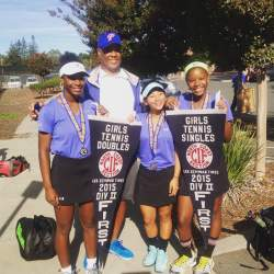 Courtesy Photo  SJND students Aysha Hayes (left), Niclole Bermudez (center right), and Azaria Hayes (right) celebrate their NCS championships with their coach Dwight Fisher.